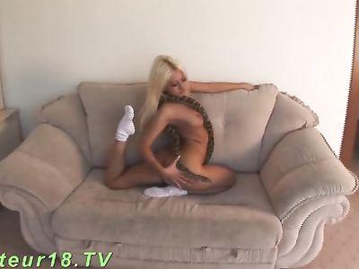 Гибкая девушка раздевается и позирует на диване с большой змеей