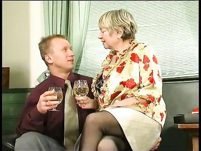 Молодчик угощает полноватую бабушку коньяком и жарит её на кресле