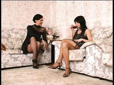 Лесбиянка в черных чулках угощает подругу бокалом вина и соблазняет её