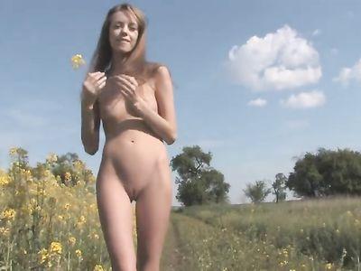 Под открытым небом на зеленом лугу русская девица гуляет обнаженной
