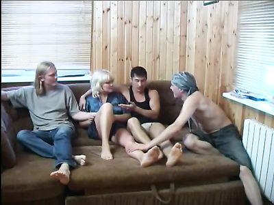 Женщина в возрасте жарится с тремя парнями на диване и кончает