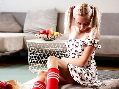 Молодая блондинка в красных гетрах ласкает свою киску на полу